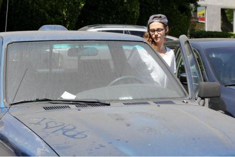 Photo widely represented as Kristen staring at the message on the hood.
